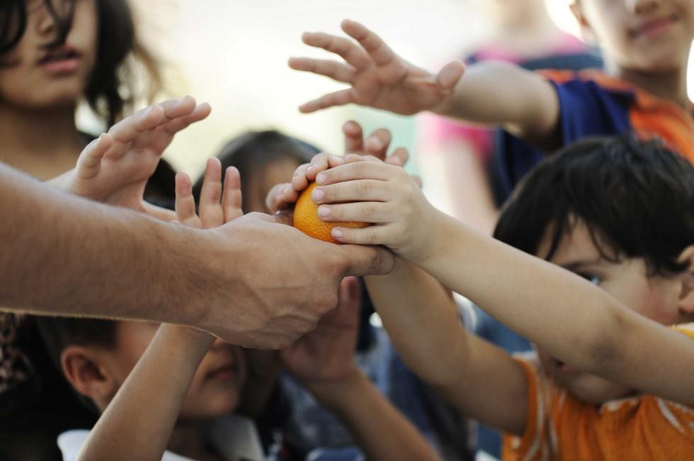 Someone handing an orange to children.